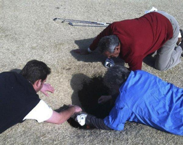 Hank Martinez, top, Ed Magaletta, right, and Russ Nobbe look into an 18-foot-deep sinkhole that golfer Mark Mihal fell into.