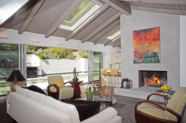 Walls of windows and skylights bring sunshine into the living room area.