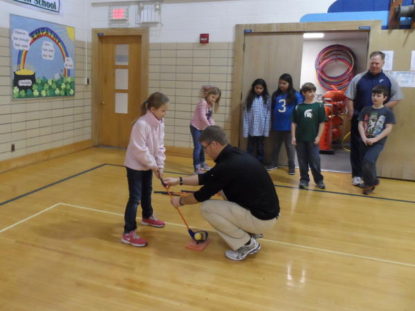 First Tee golf professional Shaun Bezilla helps Lincoln Elementary student Ellie Jones with her grip.