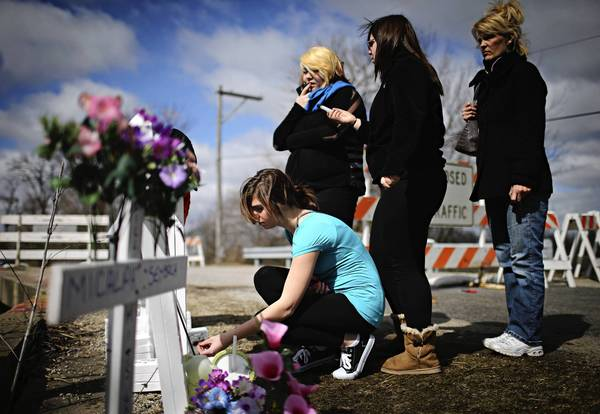 Mourners Kalli Fuller (left to right), Sami Morales, Morgan Osman and Kimberly Osman visit the crash site where four teenage victims died on Ballou Road over Forked River in Wesley Township, near Wilmington, in Will County.