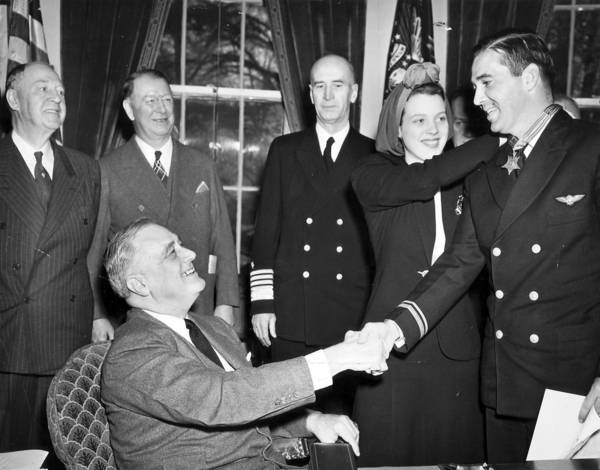 "World War II fighter pilot Lt. Cmdr. Edward ""Butch"" O'Hare, right, is congratulated by President Franklin D. Roosevelt as O'Hare's wife Rita places the Medal of Honor around his neck on April 21, 1942, during a White House ceremony in Washington, D.C."