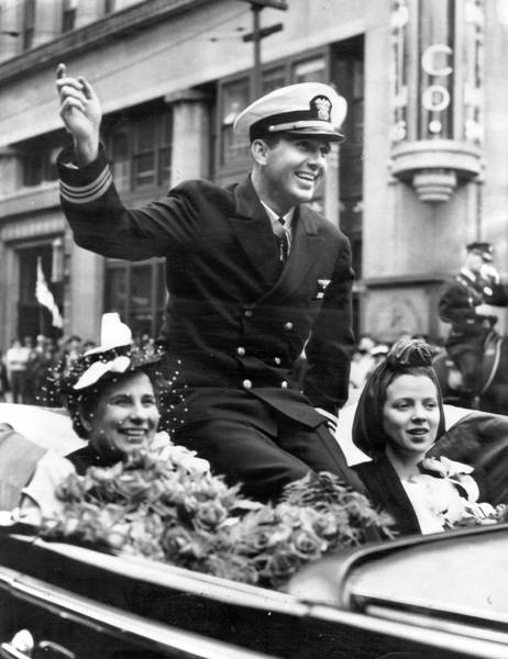 "Edward ""Butch"" O'Hare waves during a parade held in his honor in his hometown of St. Louis, Missouri. Flanking him are his mother Selma O'Hare, left, and his wife Rita O'Hare, right. Printed on Sept. 25, 1949."