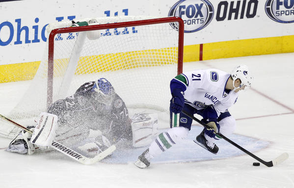 Vancouver Canucks' Mason Raymond (R) scores a goal on Columbus Blue Jackets goalie Sergei Bobrovsky during the overtime shootout period of their NHL hockey game in Columbus, Ohio March 12, 2013.  REUTERS/Matt Sullivan  (UNITED STATES - Tags: SPORT ICE HOCKEY TPX IMAGES OF THE DAY)