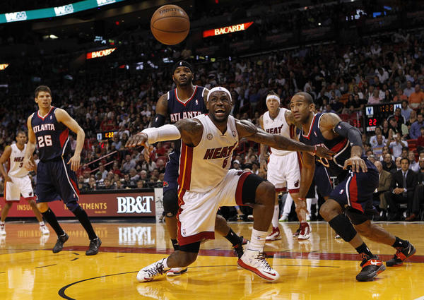 Miami Heat forward Lebron James (C) goes after a loose ball against Atlanta Hawks Kyle Korver, Josh Smith and Dahntay Jones (L-R) during their NBA game at the American Airlines Arena in Miami, Florida, March 12, 2013.   REUTERS/Robert Sullivan   (UNITED STATES - Tags: SPORT BASKETBALL TPX IMAGES OF THE DAY)