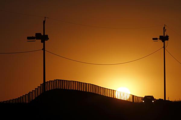 A U.S. border patrol vehicle is parked at the U.S.-Mexico border fence near Naco, AZ.