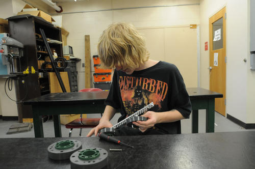 "Damek Violette, a member of the Manchester High School robotics team, takes apart a robot after school Wednsday. its parts will be used to build a new robot which will be used in practice against the team's lead entry, ""The Terminator,"" which they are taking to the world competition in Anaheim in April this year."