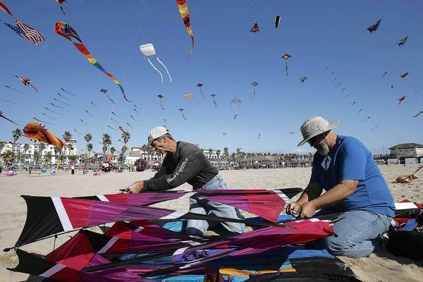 Charles Gillespi, right, works on putting together a kite called the Crimson Robe with the designer of the kite, Robert Brasington, during Kite Party 11 on Saturday on the north side of Huntington Beach Pier.