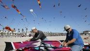 Nearly 100 people gathered at the north side of the Huntington Beach Pier on Saturday morning for one purpose — to fly kites.