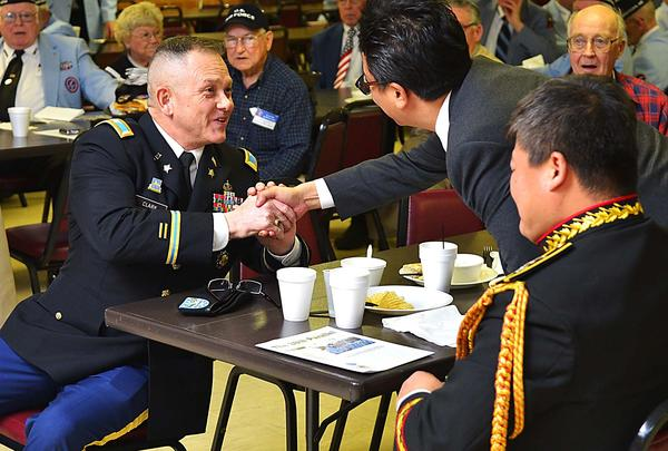 U.S. Army Col. Dave Clark shakes hands Wednesday with Ju Yong Kim, director of South Korea's Ministry of Patriots and Veterans Affairs, during a luncheon at the American Legion in Funkstown that was attended by about 65 Korean War veterans from Western Maryland and northern Virginia. Lt. Col. Kang Moon Ho, assistant defense attache in the South Korean Marine Corps based at the South Korean Embassy in Washington, D.C., looks on.