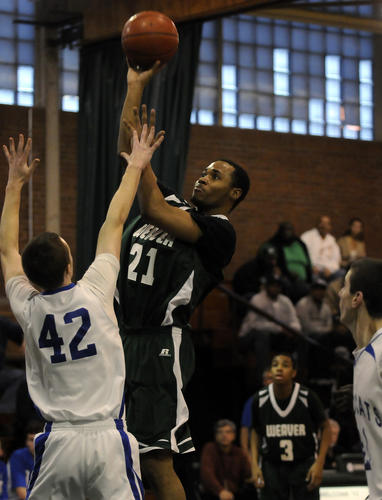 Joseph Brown of Weaver takes shot over Matthew Fuller of Old Lyme during the first half of their Class S semifinal game at Maloney High School in Meriden Wednesday night. Weaver advanced to the finals this weekend with a 69-59 victory.