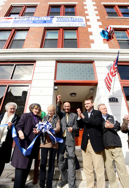 Rafie Ansari, center, pumps his fist in the air after cutting the ribbon Wednesday afternoon to officially open his Wareham Professional Center at 138 W. Washington St. in downtown Hagerstown. His wife, Diane Ansari, holds the bow. Byline: Joe Crocetta