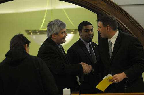 -New Britain Mayor Tim O'Brien is greeted by alderman and mayor pro tem Michael Trueworthy, right, before he gave his state of the city address in the council chambers at city hall Wednesday night. At center is  alderman Roy Centeno.