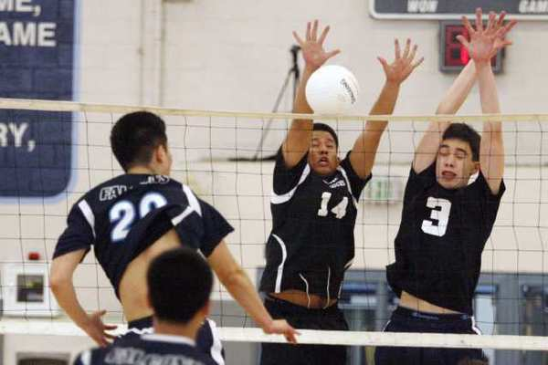 Crescenta Valley's Alex Shin, from left, spikes the ball and is blocked by Hoover's Christian Pacificador and Derek Delacruz during a game at Crescenta Valley High on Wednesday.