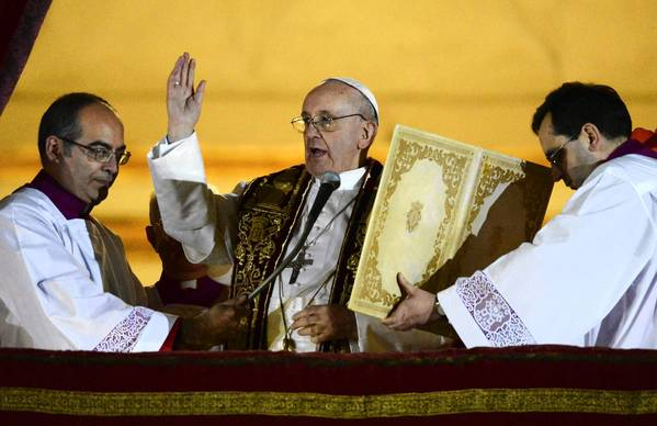 Newly elected Pope Francis, Cardinal Jorge Mario Bergoglio of Argentina offers a blessing from the balcony of St. Peter's Basilica after being elected by the conclave of cardinals.