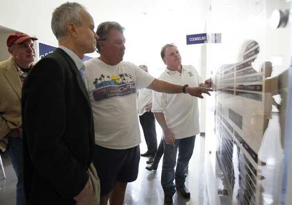 Steve Foley, left, Joseph Mulroy, Eric Tweit and Brian Theriot, right, look at the new Newport Harbor High School track and field record board outside the office at the school on Wednesday.