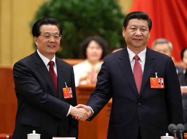 Outgoing Chinese President Hu Jintao, left, congratulates his successor, Xi Jinping, after Xi was elected to the presidency at a plenary meeting of the National People's Congress in Beijing.