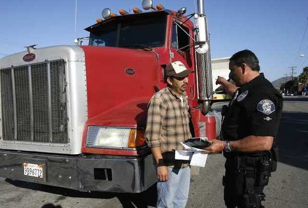Glendale officer Joe Borbon gives Jose Lizama a ticket for problems with his truck. Law enforcement set up a commercial vehicle inspection checkpoint to check trucks for mechanics and permits.