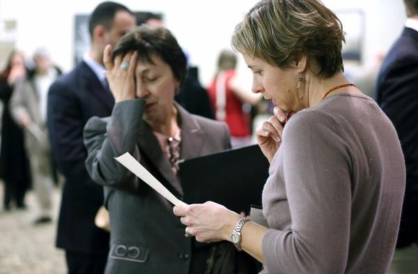 Ann Oganesian, left, of Newton, Mass., pauses as she speaks with a State Department employee about job opportunities with the federal government during a job fair in Boston.