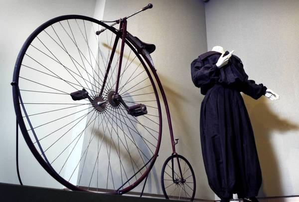 A 1879 Pope Columbia Ordinary Bicycle made in Hartford. At right is a period bicycling costume.