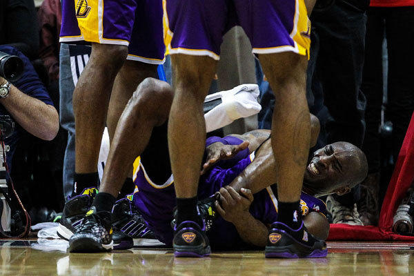 Los Angeles Lakers shooting guard Kobe Bryant (24) grabs his ankle before coming out of the game at the end of the second half against the Atlanta Hawks at Philips Arena.