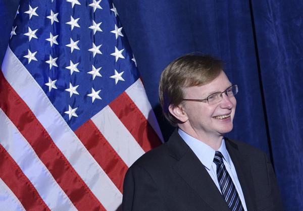 Organizing for Action head Jim Messina reacts to President Obama's remarks at the group's dinner at the St. Regis Hotel in Washington.
