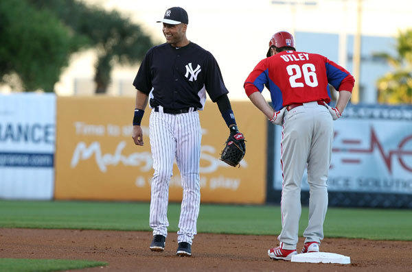New York Yankees shortstop Derek Jeter (2) smiles as he talks with Philadelphia Phillies second baseman Chase Utley (26) on second base during the first inning at George M. Steinbrenner Field.