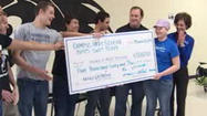 The Campus High School swim team presented a check for mroe than $5,000 to a local Make-a-Wish student.