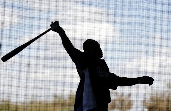Carl Crawford, who is recovering from elbow surgery, swings a bat during spring training.