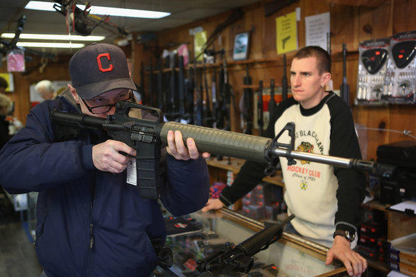 A customer checks out a weapon at a sporting goods store in Tinley Park, Ill.