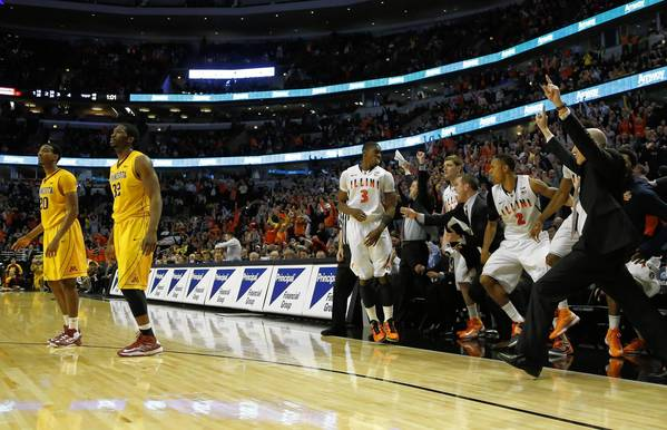 Brandon Paul (3) looks to his bench after making the winning shot over Minnesota defenders Trevor Mbakwe (32) and Austin Hollins (20).