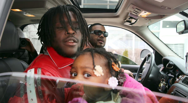 Chief Keef holds his baby after being released from juvenile detention center in Chicago.