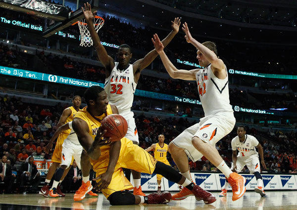 Minnesota Golden Gophers' Trevor Mbakwe (L) tries to make a pass from the floor as he is guarded by Illinois Fighting Illini's Nnanna Egwu (C) and Tyler Griffey during their NCAA men's college basketball game at the 2013 Big 10 tournament in Chicago, Illinois, March 14, 2013.