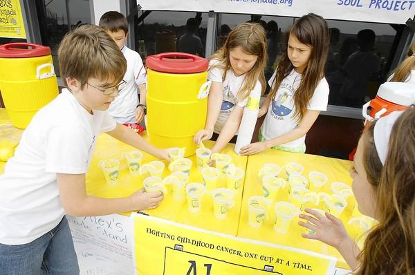 Team Sweet and Sour Sea Lions, including Sebastian Fernandez, Trevor Richardson, Maddie Graboske, Kennedy Roller and Anna Marie McIntosh, work hard to prepare more than 300 cups of lemonade during Alex's Lemonade Stand to benefit childhood cancer at El Morro School on Wednesday.