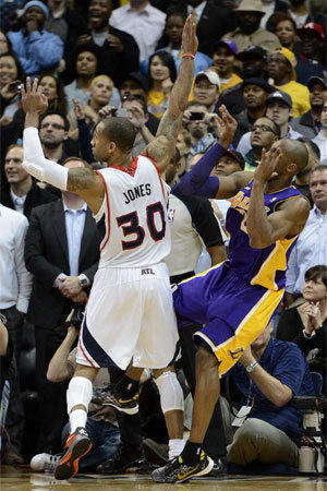 Kobe Bryant comes down on his left ankle after taking a closing-seconds shot against Atlanta Hawks forward Dahntay Jones.