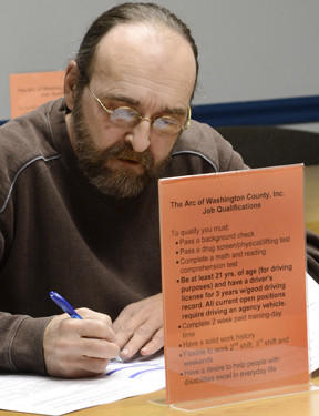Timothy Faulder of Hagerstown fills out an application at a job fair Thursday held at the Arc of Washington County.