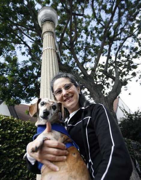 Glendale resident Rebecca Rees and her dog Charlie stand next to the lamppost she saved by chaining herself to it when the city wanted to remove it back in 1994.