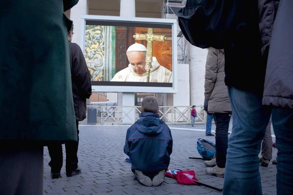 People gathered at St. Peter's Square watch Pope Francis' Mass with cardinals in the Sistine Chapel.