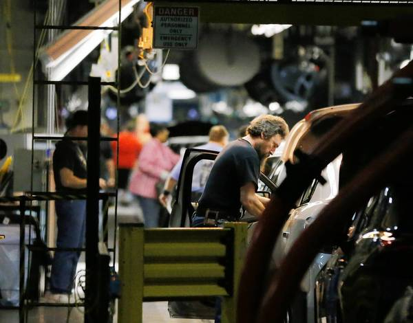 Workers assemble cars along a line at the General Motors Fairfax plant in Kansas City, Kan. Consumer spending grew at a surprisingly quick pace in February, pushed upward by robust demand for cars and building materials.