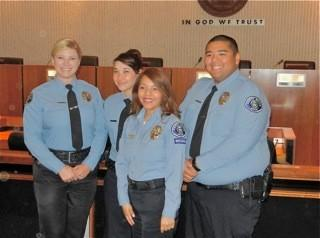 New Community Service Specialists Amanda Seers, Jessica Jung and Alec Tanchauco receive their badges, along with Records Shift Supervisor Lidian Estecoc, front.