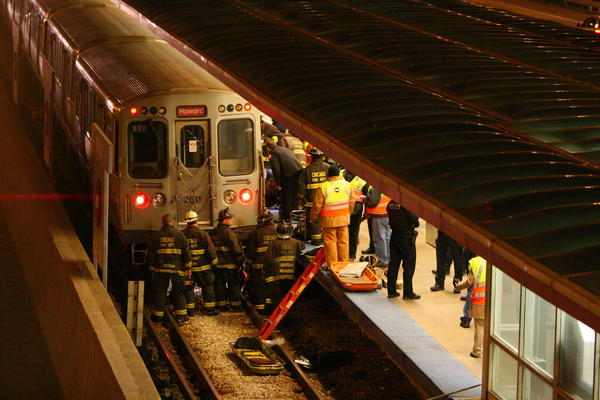 Chicago firefighters work to remove a person pinned in on the CTA tracks at the 87th Street Red Line stop.