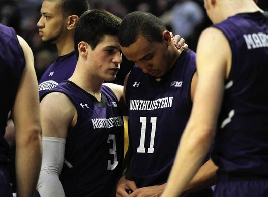 Northwestern senior Reggie Hearn is consoled by Dave Sobolewski at end of 73-59 loss to Iowa.