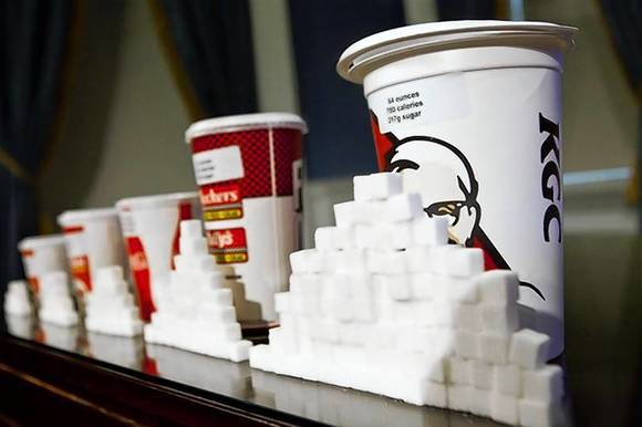 A 64-ounce drink is displayed alongside other soft drink cup sizes at a news conference at City Hall in New York