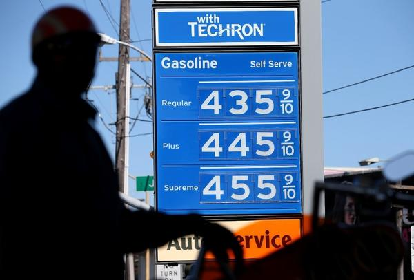 Gas prices are displayed as a motorcyclist fuels his motorcycle at a Chevron gas station in San Francisco.