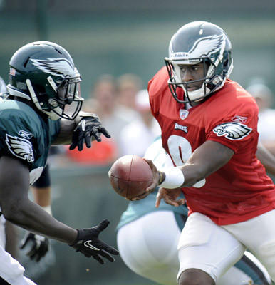 Vince Young hands off to Ronnie Brown, left, at Eagles training camp Saturday.