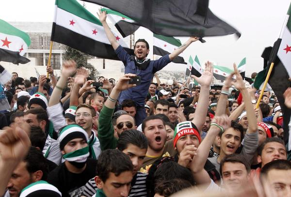 Hundreds of people gather in front of the Syrian embassy in Amman, Jordan, to mark the second anniversary of the fighting between Syrian opposition forces and forces loyal to President Bashar Assad.