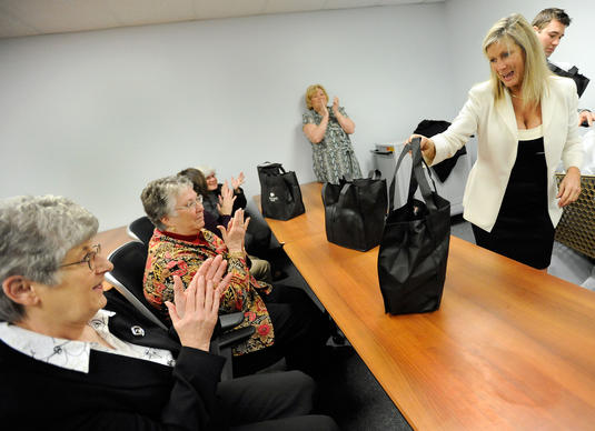 Nancy Hafford, right, executive director of the Towson Chamber of Commerce, hands gift bags to Peggy Johnson, left, and Judy Opfer, second from left, both Baltimore County Public Schools employees who recently moved into the Jefferson Building on Friday, March 15. The bags contained gifts and coupons donated by local businesses.
