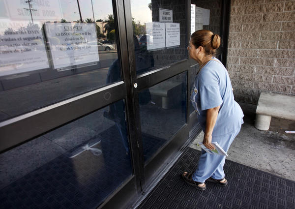 Olga Menendez peers into the dark offices of the Department of Motor Vehicles at 3615 S. Hope Street in Los Angeles. Signs on the door indicate the office is closed due to a furlough day.