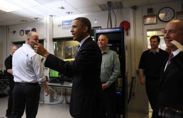 President Barack Obama greets a researcher as he tours the Argonne National Laboratory's Advanced Powertrain Research Facility.