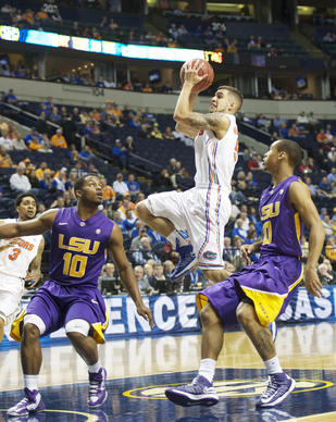 Florida Gators guard Scottie Wilbekin (5) shoots over LSU Tigers guard Andre Stringer (10) and guard Charles Carmouche (0) during the quarterfinals of the SEC tournament at Bridgestone Arena.