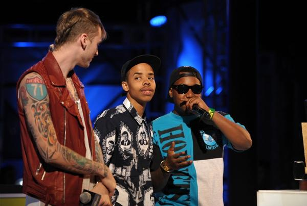 Host Machine Gun Kelly, left, presents the Breaking Woodie to Earl Sweatshirt, center, on stage at the mtvU Woodie Awards on Thursday, March 14, 2013, in Austin, Texas. Speaking at right is Domo Genesis.